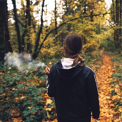 woman walking in woods moking marijuana cigarette
